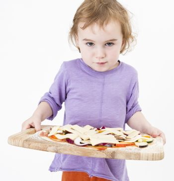 cute young girl holding plate with fresh pizza. studio shot in grey background