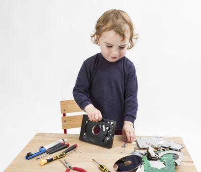 preschooler with computer parts on wooden desk. studio shot in light grey background