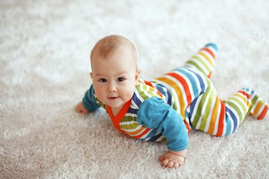 6 months baby lying down on a soft cozy carpet and looking at camera