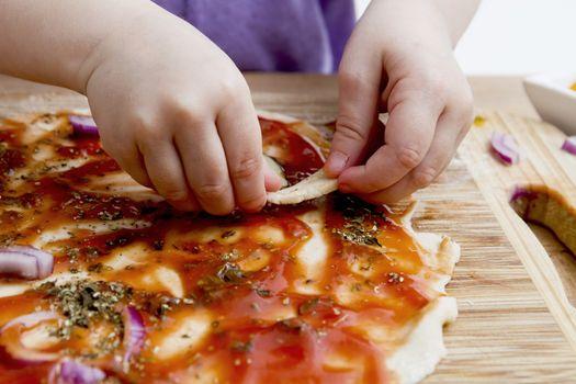 small hands preparing fresh pizza. Studio shot