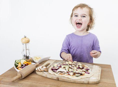 cute child making fresh pizza . studio shot isolated on grey background