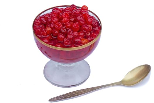 Bright red berries in a crystal vase filled with sugar syrup. Presented on a white background.