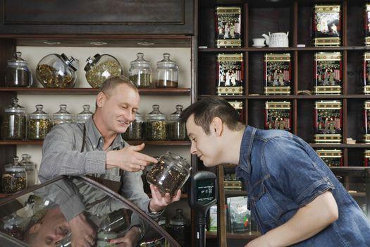 Tea Shop Owner Showing Tea to Customer