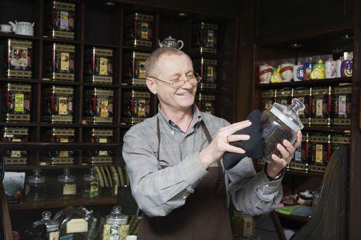 Tea Shop Owner Dusting Jar of Tea