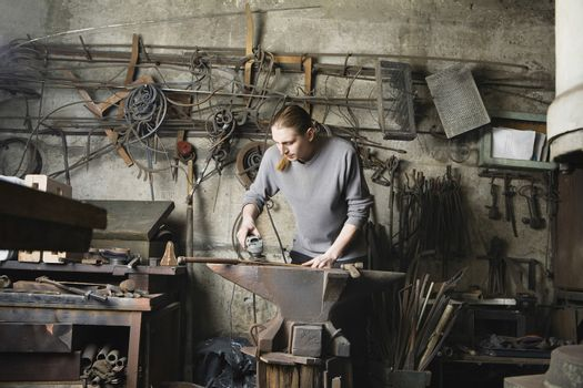 Young male blacksmith working in workshop