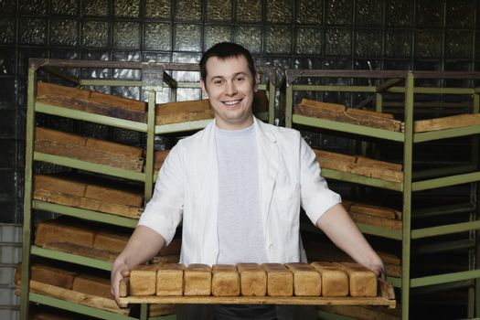Baker Carrying Loaves of Fresh Bread