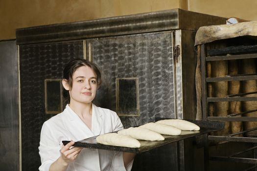 Baker Carrying Loaves of Bread Dough to Bake