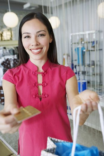Portrait of a happy young woman paying for purchase with credit card