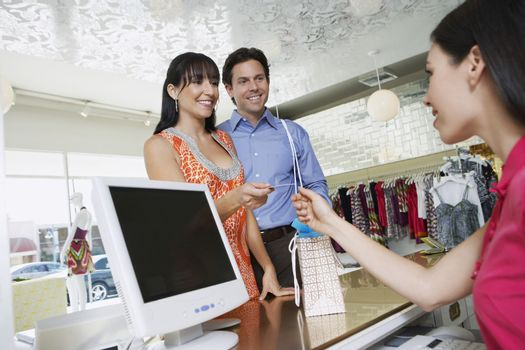 Happy couple paying for merchandise with credit card in clothing store