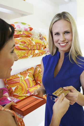 Beautiful blonde woman paying for purchase with credit card in store