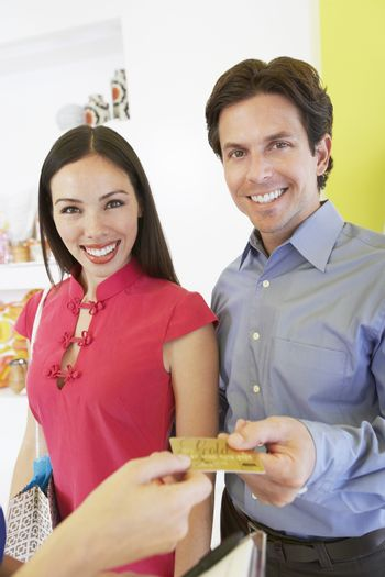 Portrait of a happy couple paying for purchase with credit card
