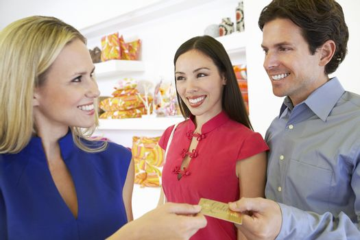 Happy couple handing over credit card to saleswoman for payment of purchase