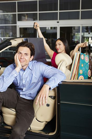 Portrait of a displeased man with happy shopaholic woman sitting in a convertible