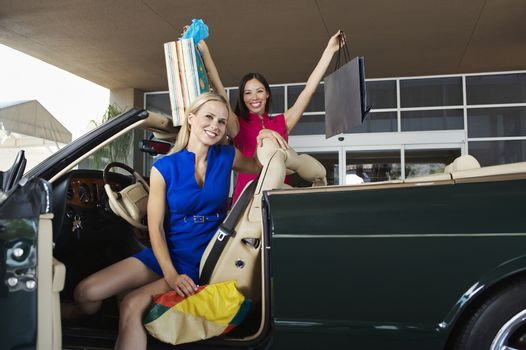 Portrait of shopaholic female friends in a convertible