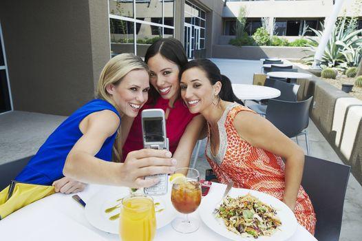 Happy female friends taking self portrait at restaurant