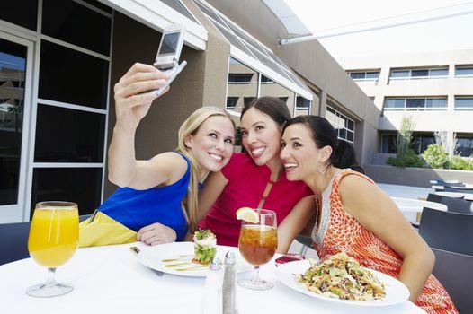 Beautiful female friends taking self portrait at restaurant