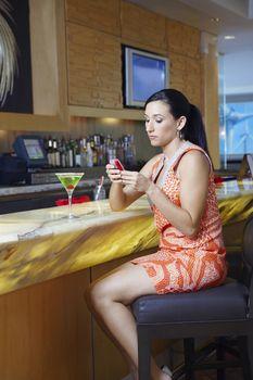 Beautiful woman text messaging at the bar counter