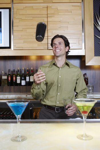 Handsome bartender tossing shaker in the air at bar counter