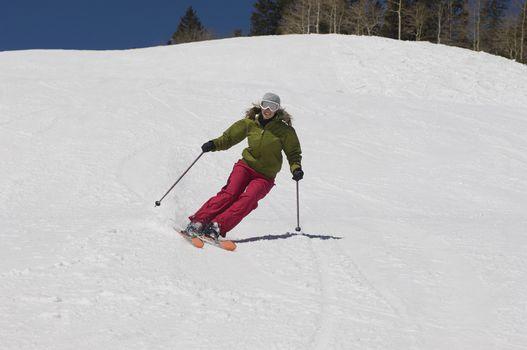 Full length of woman skiing down ski slope