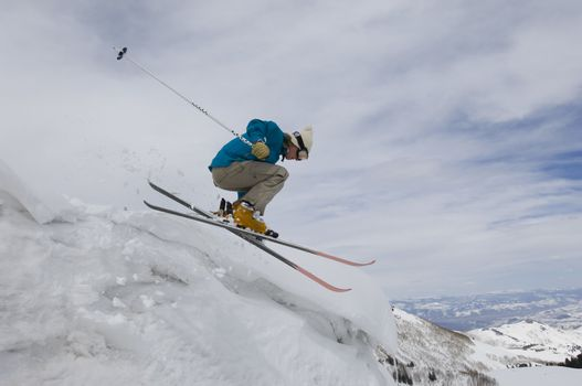 Side view of a female skier jumping off icy overhang