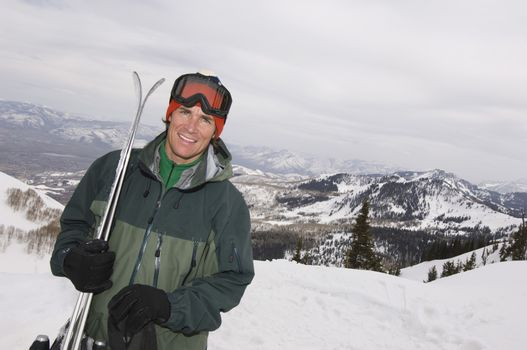 Portrait of a handsome male skier standing on mountain with skis