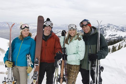 Portrait of skiers with skis standing on mountain