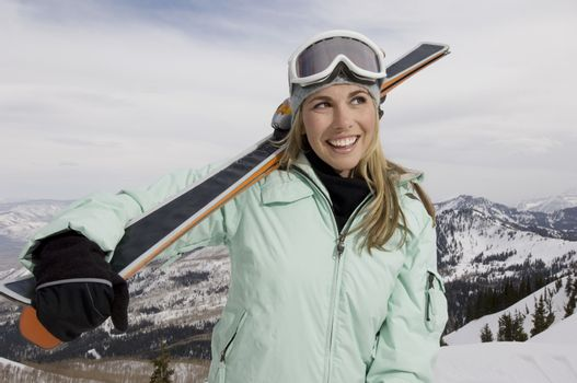 Cheerful female skier with skis looking away while standing on mountain