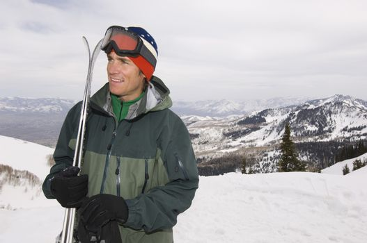 Happy male skier with skis looking away while standing on landscape