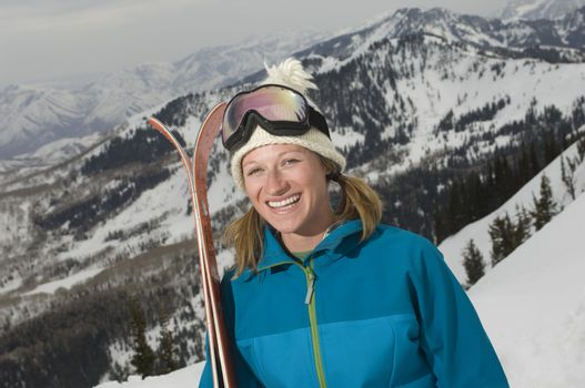 Portrait of a cheerful female skier holding skis on mountain