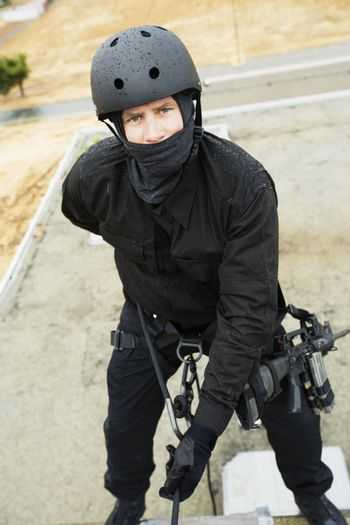 Portrait of a SWAT team officer rappelling from building