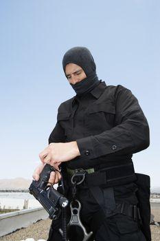 SWAT team officer loading pistol against clear sky