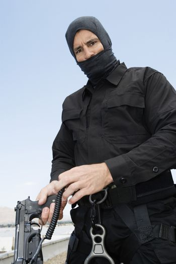 Portrait of a SWAT team officer with an automatic pistol against clear sky