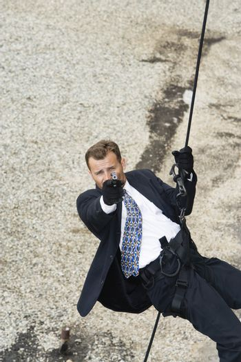 Portrait high angle shot of a spy rappelling and aiming gun