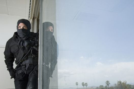 Swat team officer standing by glass window