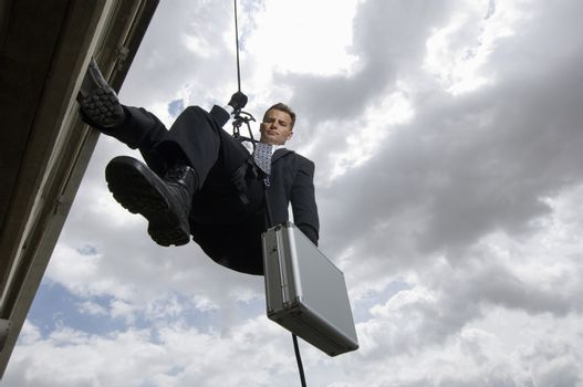 Low angle view of a spy rappelling with suitcase against cloudy sky