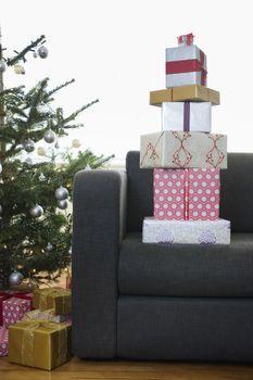 Stack of Christmas presents on sofa
