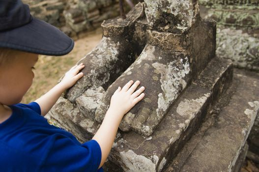 Child Looking at Feet of Ancient Statue