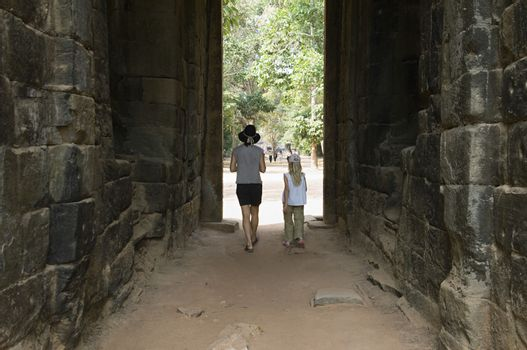 Woman and Girl Walking Through Passage in Ancient Building