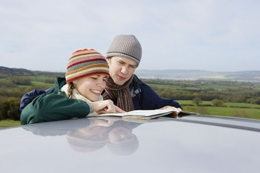 Happy young couple wearing knit hats while reading map by car in countryside