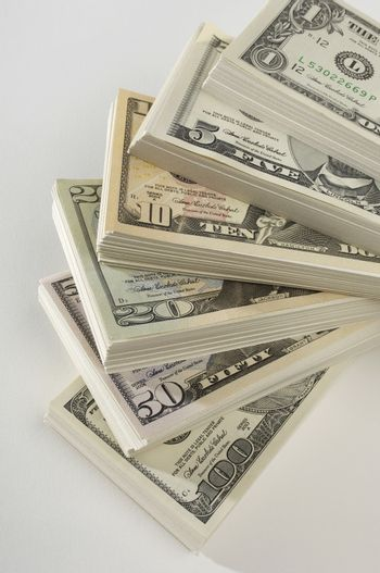 Variety of dollars stacked over white background