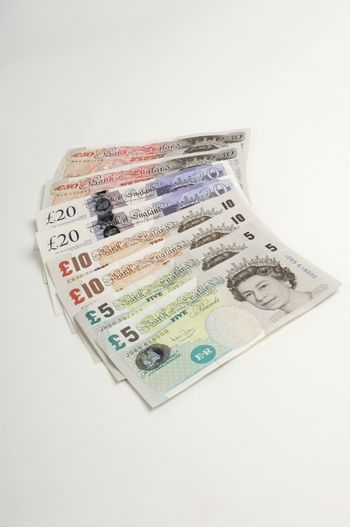 British paper currency fanned on white background