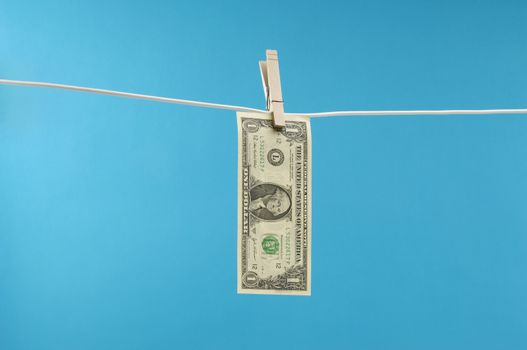 American dollar bill pinned on a clothesline over blue background