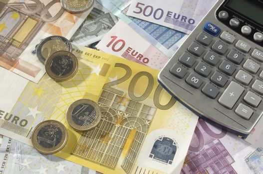 Calculator and coins on Euro notes