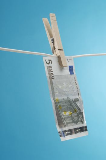 Euro note pinned on a clothesline against blue background