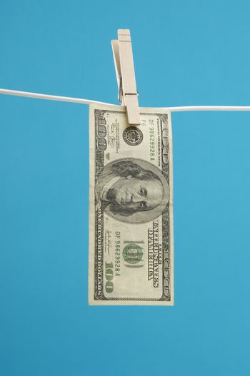 American hundred dollar bill pinned on a clothesline over blue background