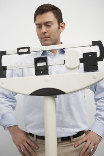 Man standing on weighing scales in hospital