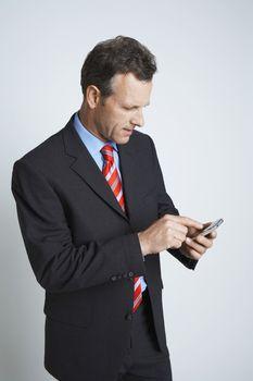 Studio shot of businessman text messaging