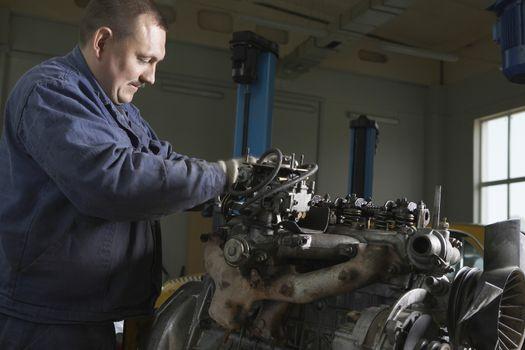 Side view of mechanic working on motor in garage