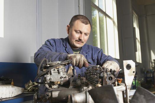 Mechanic working on motor in garage