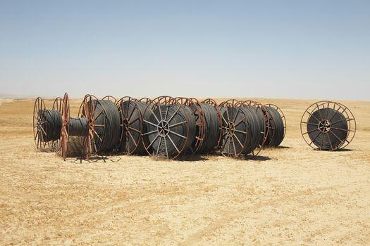 Spools of irrigation hose on arid landscape against clear sky